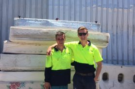 two men smiling standard in front of a pile of mattresses