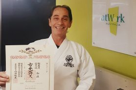 man holding his certificate in black belt in front of an atWork Australia wall sign