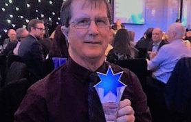 atWork Australia employee holding an award