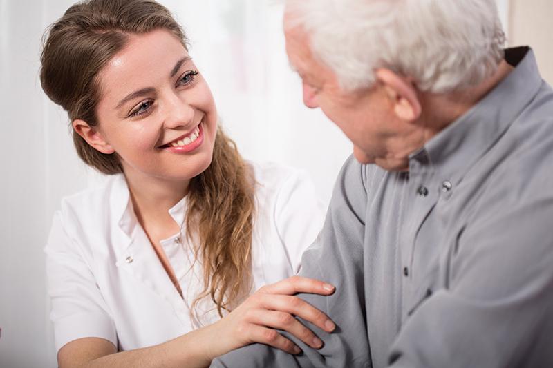 Smiling worker assisting senior man