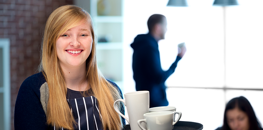 Young female waitress carrying a tray of coffees and smiling at the camera