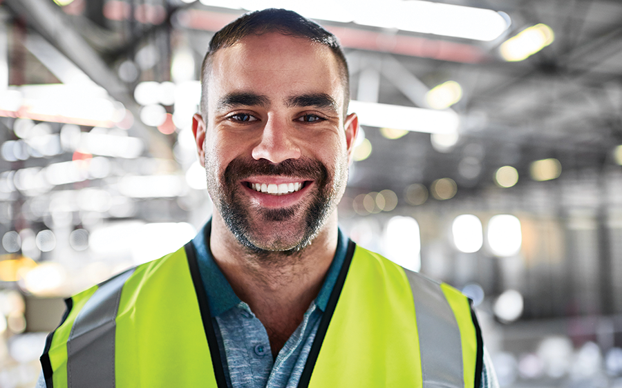 Young male factory worker smiling at camera