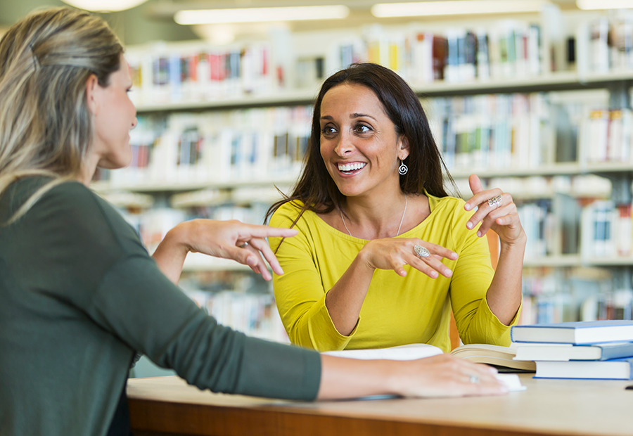 Two woman talking at a table in the middle of a library