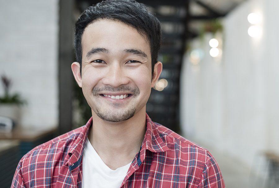 Casual young Asian businessman smiling towards camera