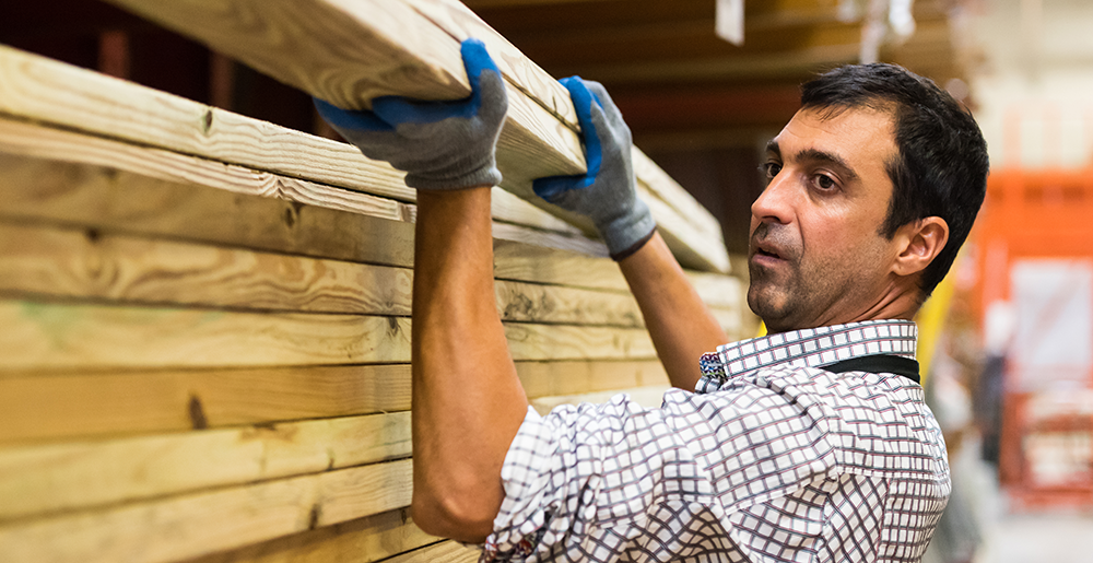 Ethnic male working in a timber yard, lifting planks of wood