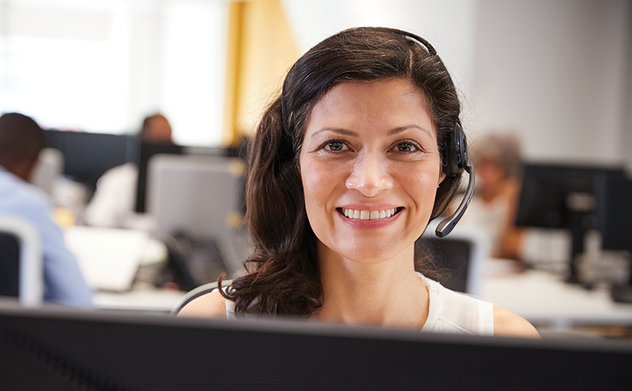 Woman smiling at the camera and working in a call centre