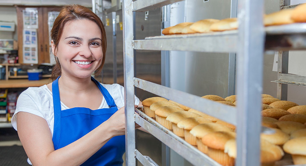 Young female baker pulling out a row of muffins