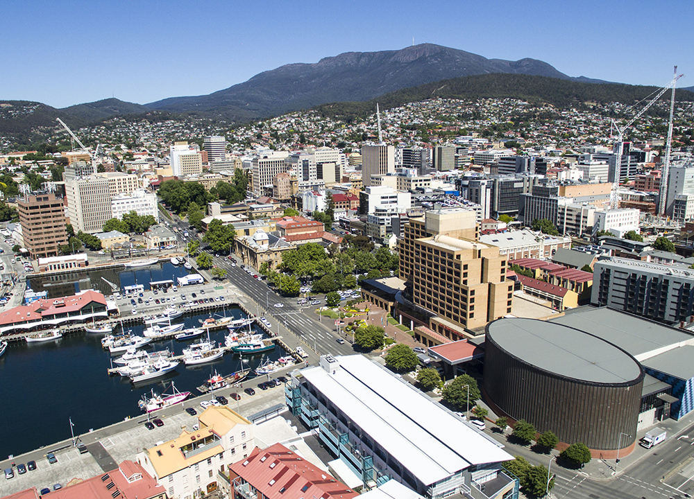 Aerial shot of Hobart featuring featuring a majestic Mount Wellington/ Kunanyi and construction cranes